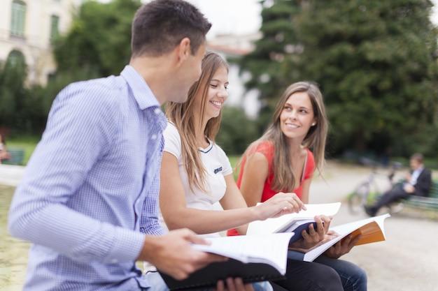 Retrato al aire libre de tres estudiantes sonrientes que estudian en un parque Foto Premium