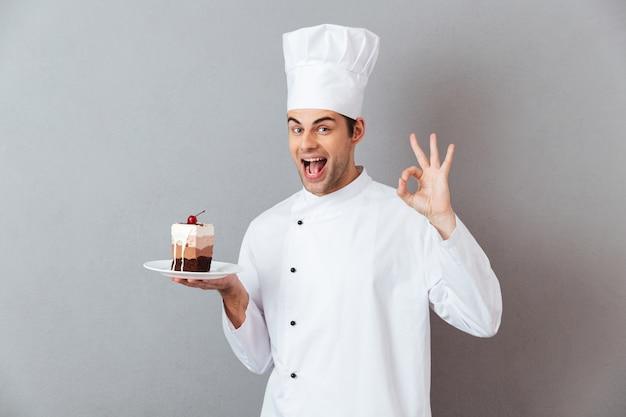 Retrato de un alegre chef hombre feliz vestido con uniforme Foto gratis