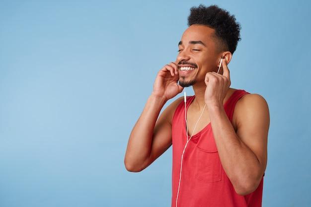 Retrato de alegre joven afroamericano se siente genial, usa auriculares, cierra los ojos y disfruta de un nuevo álbum de tu banda favorita, aislado. Foto gratis