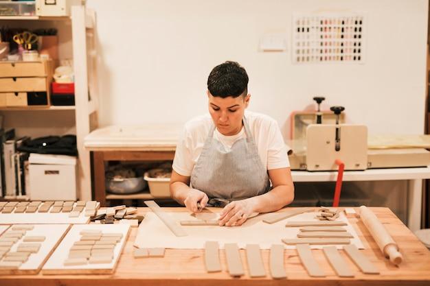 Retrato de alfarero femenino cortando la arcilla en forma rectangular en mesa de madera Foto gratis