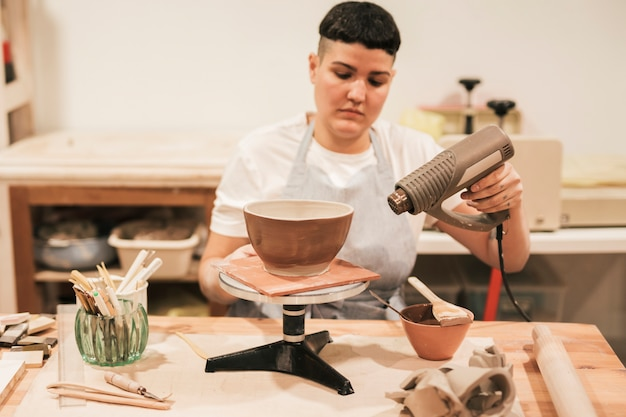 Retrato de un alfarero femenino secando la pintura con secador en el taller Foto gratis
