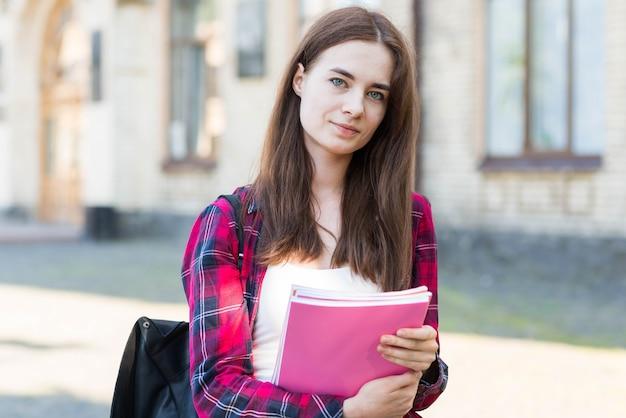 Retrato de alumna con libro en ciudad Foto gratis