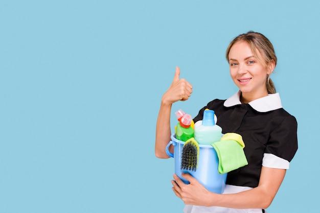 Retrato de ama de llaves feliz mostrando el pulgar hacia arriba gesto con equipos de limpieza en el cubo mirando a la cámara Foto gratis