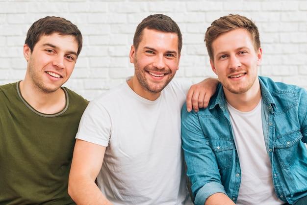 Retrato de amigos masculinos sonrientes que miran la cámara contra la pared de ladrillo blanca Foto gratis