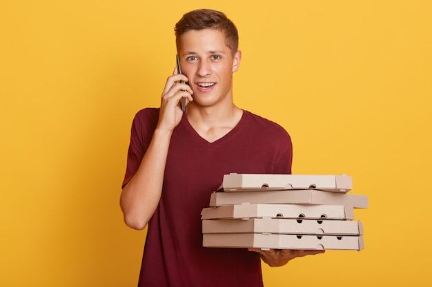 Retrato de un apuesto joven adolescente rubio con teléfono inteligente y cajas con comida, trayendo orden, llamando a un cliente Foto gratis
