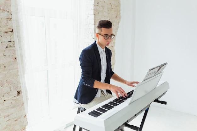 Retrato de un apuesto joven mirando la hoja musical tocando el piano Foto gratis