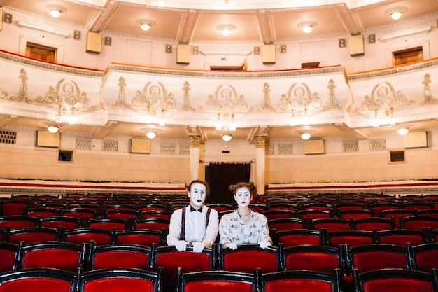 Retrato del artista de mimo masculino y femenino sentado en la silla roja en el auditorio Foto gratis