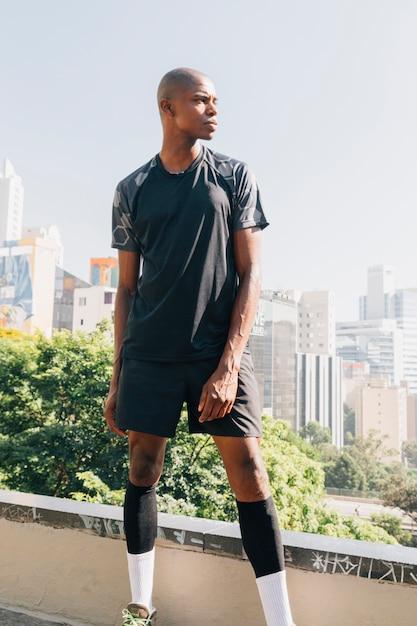 Retrato de un atleta corredor masculino de pie en la azotea Foto gratis