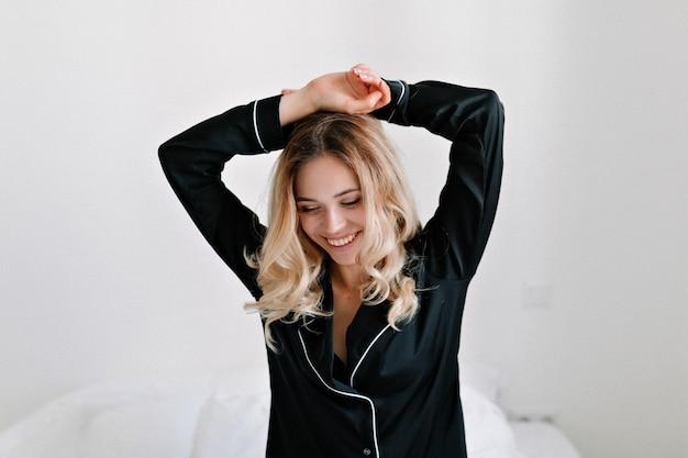 Retrato de atractiva chica encantadora emocionada en ropa de dormir negra se despierta en la cama por la mañana en el apartamento moderno. Foto gratis
