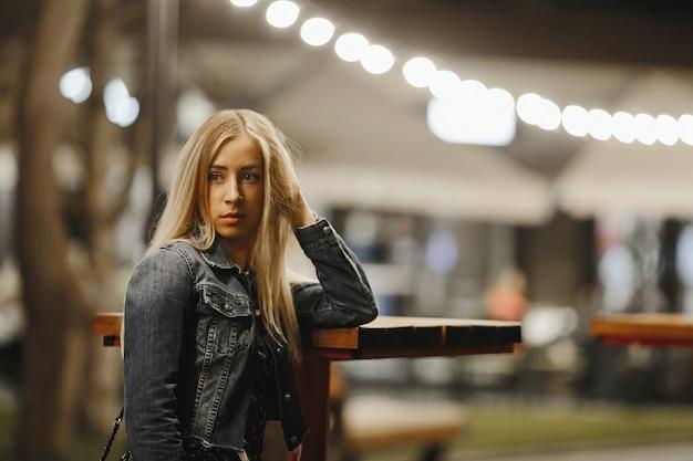 Retrato de una atractiva joven rubia caucásica cerca de la mesa de café alta al aire libre está mirando seriamente al lado vestida con una chaqueta de jeans bajo la iluminación del festón Foto gratis