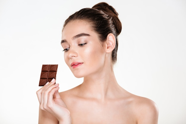 Retrato de atractiva mujer semidesnuda con cabello oscuro disfrutando de dulces comiendo barra de chocolate con leche Foto gratis