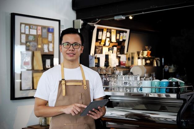 Retrato del barista asiático que sostiene la tableta digital en el contador en cafetería Foto Premium