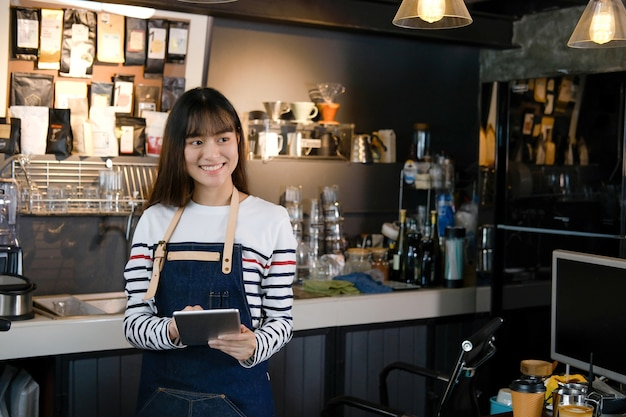 Retrato del barista asiático sonriente que sostiene la tableta digital en el contador en cafetería Foto Premium
