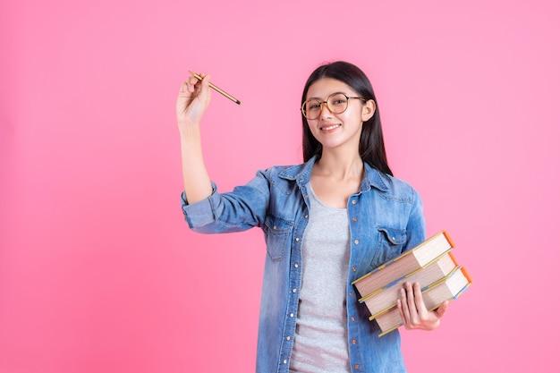 Retrato bastante adolescente femenina sosteniendo libros en su brazo y usando lápiz en rosa, concepto de educación Foto gratis
