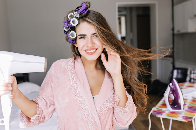 Retrato bastante joven en bata de baño rosa con rizos en la cabeza en casa. ella secando el cabello, sonriendo. Foto gratis
