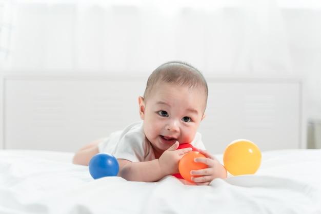 Retrato de un bebé gateando en la cama en su habitación y jugando a la pelota de juguete, adorable bebé en blanco dormitorio soleado. Foto Premium