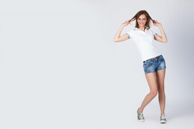 Retrato de bella joven sonriente de pie chica en una camiseta blanca, pantalones cortos azules y zapatillas de deporte aisladas Foto Premium