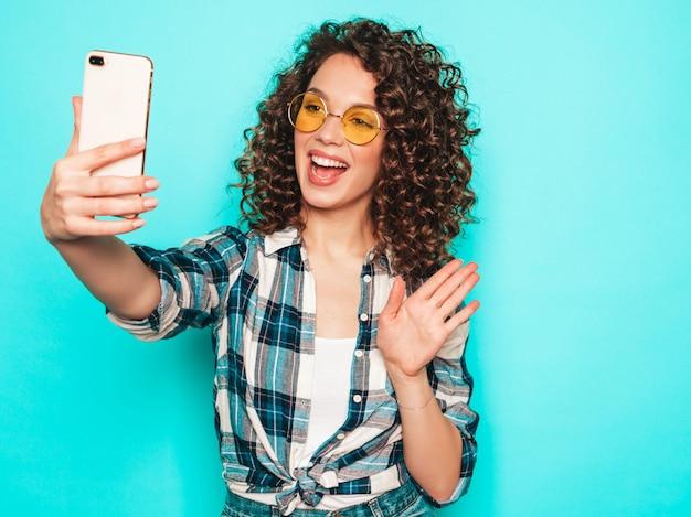 Retrato de la bella modelo sonriente con peinado afro rizos vestido con ropa hipster de verano.la mujer de moda divertida y positiva hace selfie Foto gratis