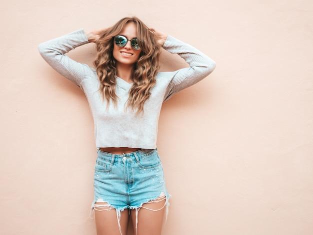 Retrato de la bella modelo sonriente vestida con pantalones cortos de verano hipster jeans ropa Foto gratis