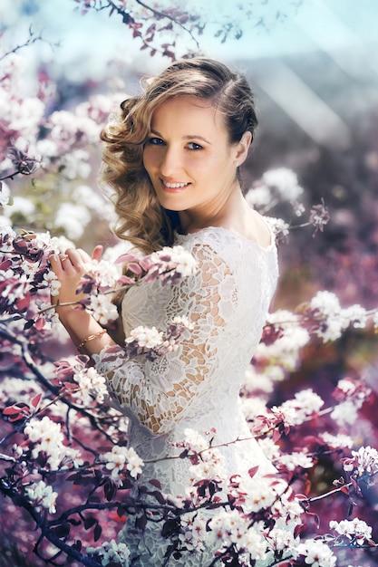 Retrato de una bella mujer en un jardín floreciente Foto Premium