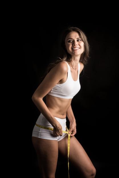Retrato de una bella mujer joven midiendo su tamaño de figura con cinta métrica Foto gratis