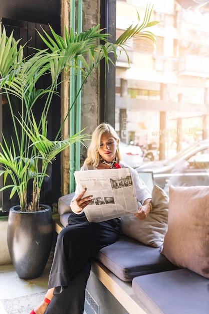 Retrato de una bella mujer joven sentada en una cafetería leyendo un periódico Foto gratis