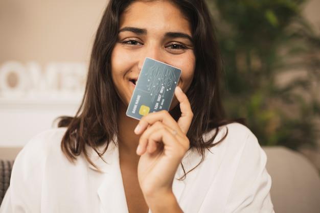 Retrato de una bella mujer mostrando una tarjeta de crédito Foto gratis