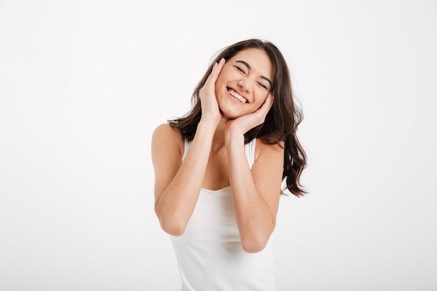 Retrato de una bella mujer vestida con una camiseta sin mangas riendo Foto gratis