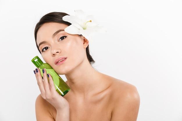 Retrato de belleza de buena mujer asiática con flor en el pelo con loción corporal o aceite de spa en la mano, aislado en blanco Foto Premium