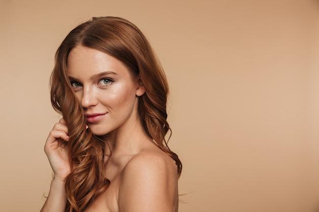 Retrato de belleza de misterio sonriente mujer de jengibre con cabello largo posando de lado y mirando Foto gratis