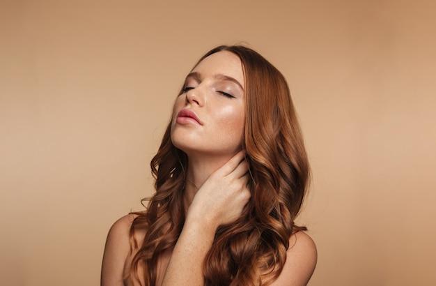 Retrato de belleza de misteriosa mujer de jengibre con cabello largo posando con los ojos cerrados mientras toca su cuello Foto gratis