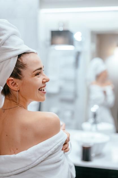 Retrato de belleza de mujer bonita vistiendo una toalla de baño blanca Foto gratis