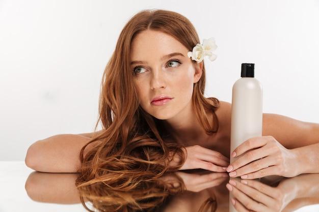 Retrato de belleza de mujer de jengibre con flores en el pelo sentado junto a la mesa del espejo con una botella de loción mientras mira hacia otro lado Foto gratis