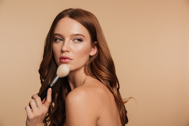 Retrato de belleza de mujer sensual de jengibre con cabello largo posando hacia los lados mientras mira hacia otro lado y sostiene el cepillo de cosméticos Foto gratis
