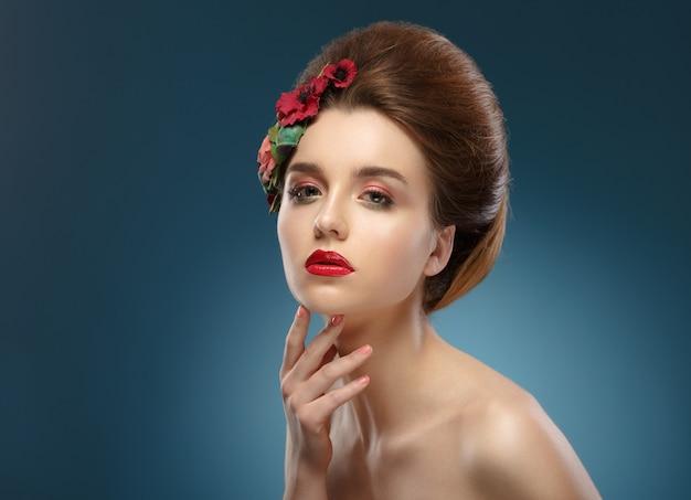 Retrato de belleza mujer tocando su rostro. hermosa mujer con maquillaje de colores y flores en el pelo Foto Premium