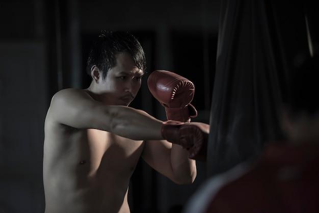Retrato de un boxeo practicante del hombre asiático joven en un bolso de perforación en el gimnasio. Foto gratis