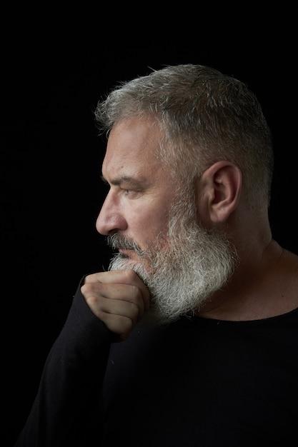 Retrato de un brutal hombre de cabello gris con una exuberante barba gris y cara estricta sobre un fondo negro, enfoque selectivo Foto Premium