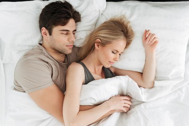 Retrato de calma guapo pareja durmiendo en la cama Foto gratis