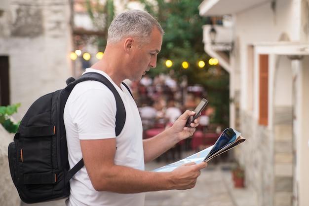 Retrato del caminante masculino maduro que usa el teléfono elegante al aire libre. Foto gratis