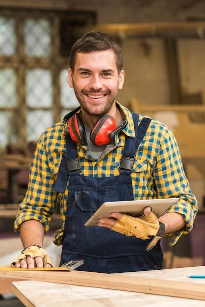 Retrato de un carpintero de sexo masculino sonriente que sostiene la tableta digital en la mano que mira la cámara Foto gratis