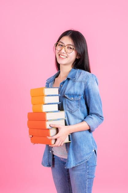 Retrato chica guapa adolescente sosteniendo la pila de libros y smiley en rosa, concepto de educación teenge Foto gratis