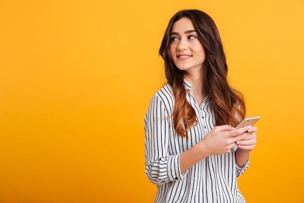 Retrato de una chica joven y bonita con teléfono móvil Foto gratis