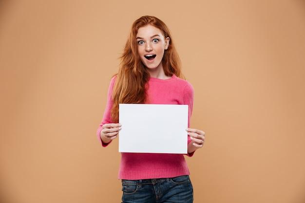Retrato de una chica pelirroja bonita emocionada con cartel blanco en blanco Foto gratis