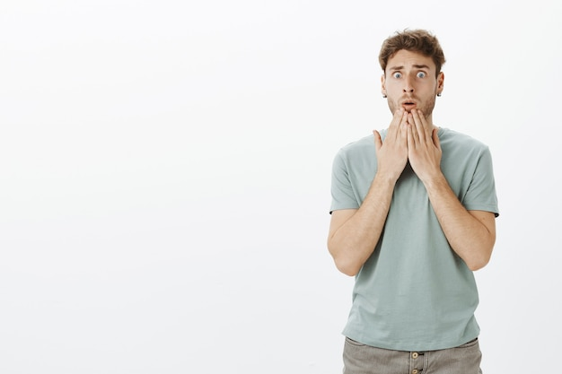 Retrato de chico atractivo sorprendido preocupado en camiseta casual, sosteniendo las palmas sobre la boca y mirando nerviosamente, sorprendido con terrible accidente Foto gratis