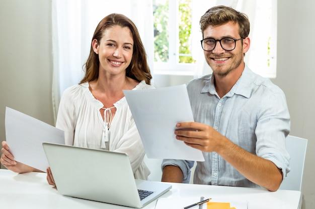 Retrato de colegas masculinos y femeninos discutiendo el documento en la oficina Foto Premium