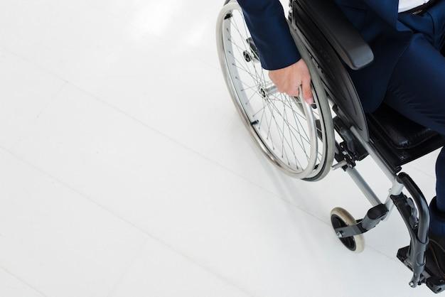 Retrato de un colegas sonrientes de pie detrás del hombre sentado en silla de ruedas Foto gratis