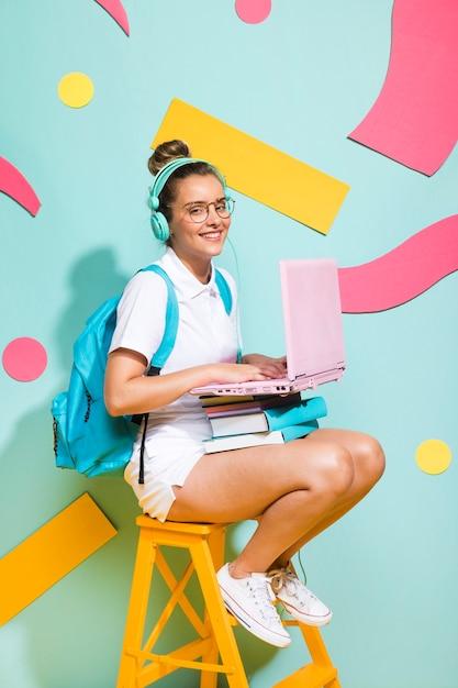 Retrato de colegiada estudiando con portátil Foto gratis
