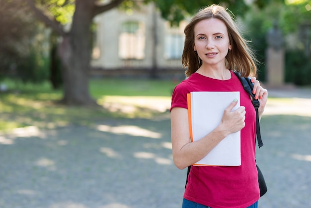 Retrato de colegiada con libros en el parque Foto gratis
