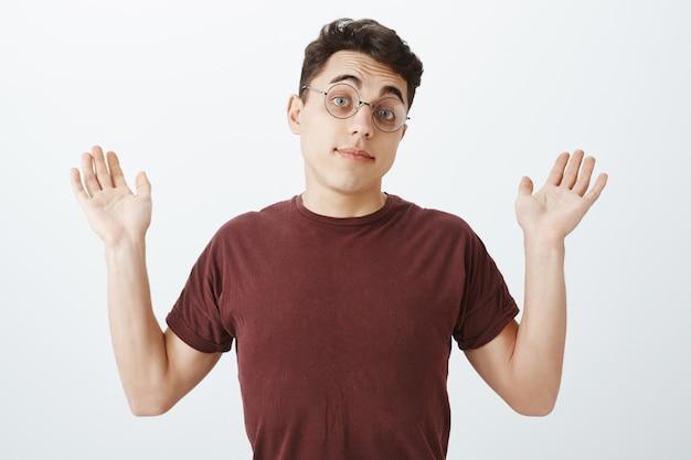 Retrato de compañero de trabajo masculino europeo inconsciente descuidado en gafas redondas y camiseta Foto gratis
