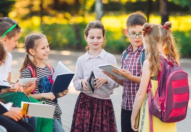 Retrato de compañeros felices. compañeros de clase que se sientan con los libros en un banco de madera en un parque de la ciudad y que estudian en día soleado. Foto Premium